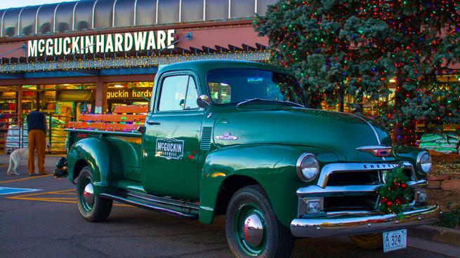 a green truck parked in front of a building