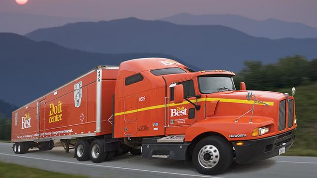 a large orange truck with a mountain in the background