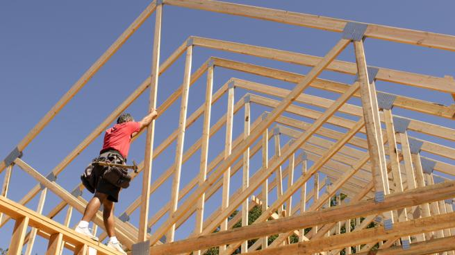 a person riding on top of a wooden fence