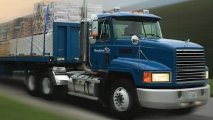 a large blue truck is driving down the road