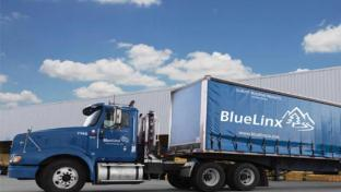 a large blue truck is parked on the side of a road